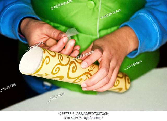 Close-up of hands putting tape onto a wrapped present