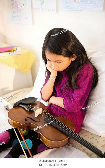 Pouting Vietnamese girl holding violin in bedroom