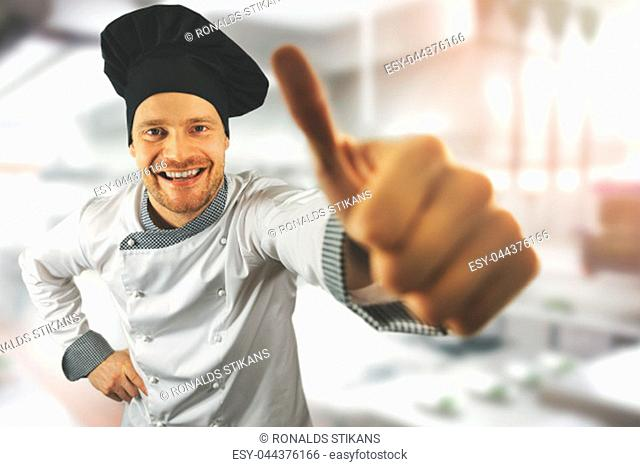 young happy chef with thumb up at restaurant kitchen