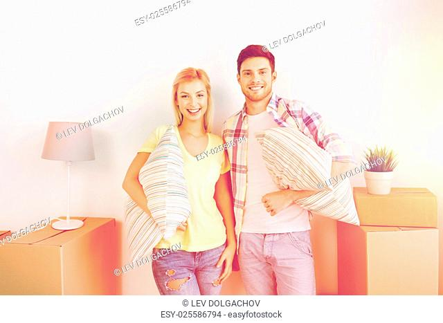 home, people, repair and real estate concept - smiling couple with big cardboard boxes and stuff moving to new place