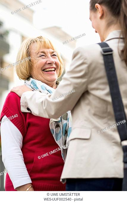Portrait of laughing senior woman communicating with her granddaughter
