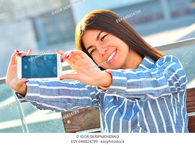 Young beautiful girl makes selfie and she is sitting on a bench in the city, the sunny day