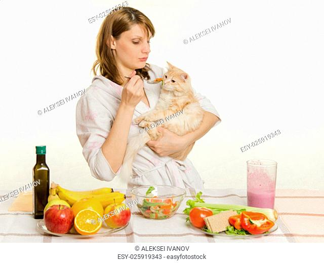 Young beautiful girl in a bathrobe prepares vegetarian salad from vegetables and greens isolated on white background