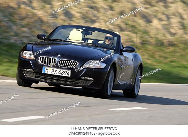 BMW Z4 3.0 si Roadster, model year 2006-, black, driving, diagonal from the front, frontal view, country road, open top
