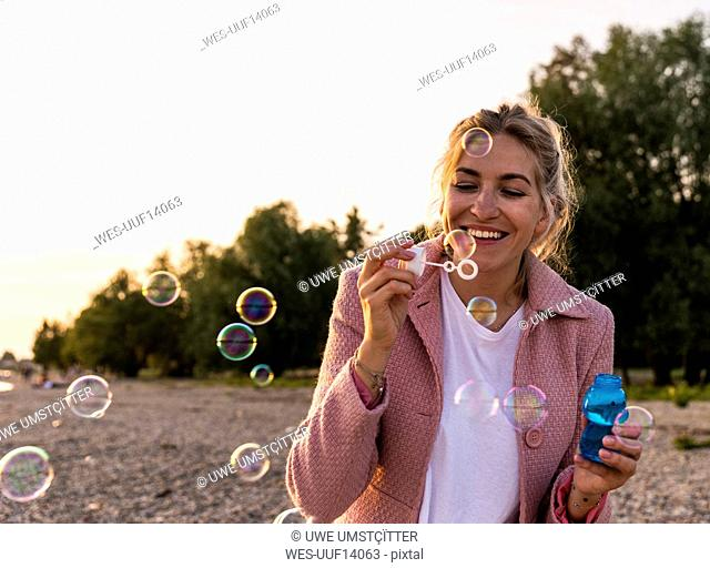 Laughing blond woman and soap bubbles