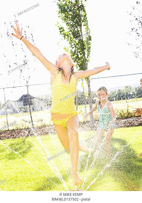 Caucasian girls playing in sprinkler in backyard