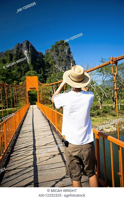 A bridge leads to caves outside of Vang Vieng; Laos