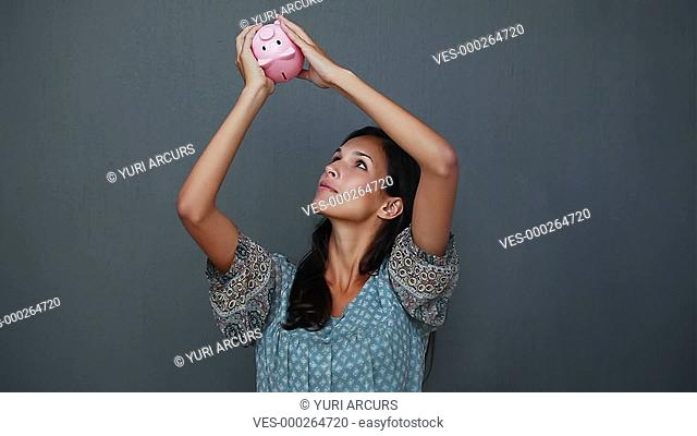 Cute young woman shaking her piggybank and looking to see if there is money inside