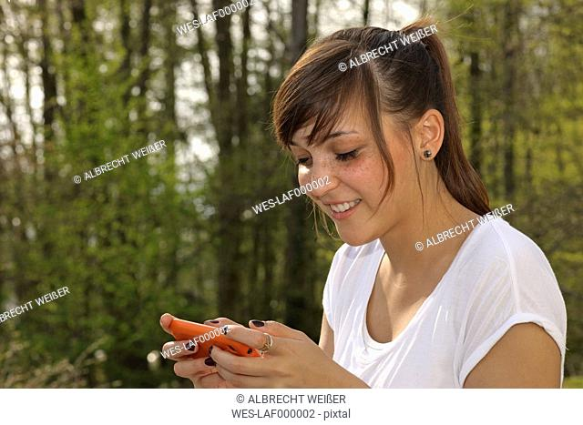 Germany, Baden Wuerttemberg, Young woman typing sms and playing on phone