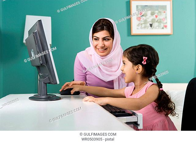 Arab mother and daughter in front of a computer
