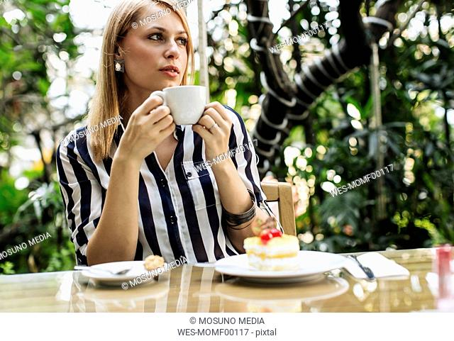 Woman sitting at sidewalk cafe with cake and cup of coffee