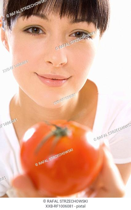 young woman holding one tomato