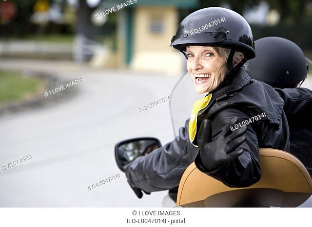 A senior couple on a motorbike