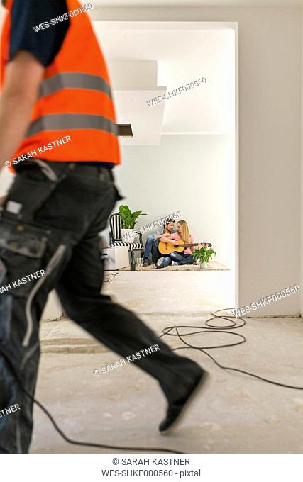 Couple with guitar sitting on the floor of their new home while man working in the foreground