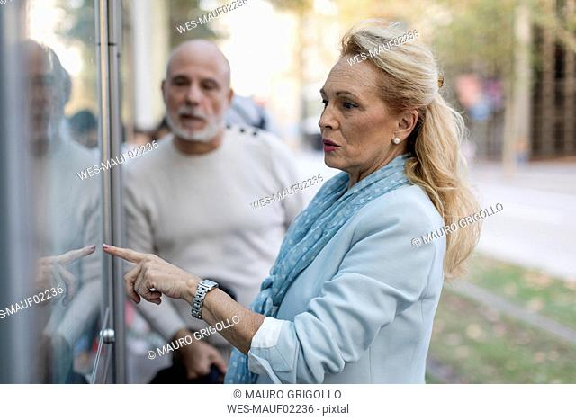 Spain, Barcelona, senior couple checking the timetable at tram stop in the city