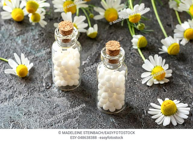 Bottles of homeopathic remedies with fresh chamomile flowers