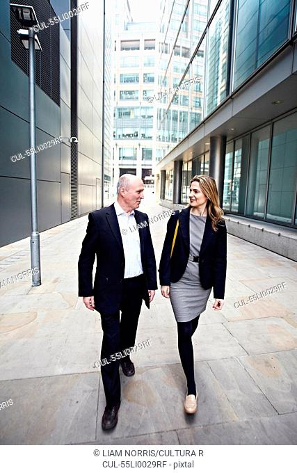 Businessman and businesswoman walking past office buildings