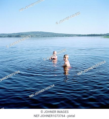 Two children swimming in lake