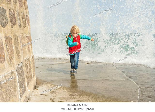 Germany, Mecklenburg-Western Pomerania, Ruegen, Sassnitz, Excited boy on pier running away from splashing water