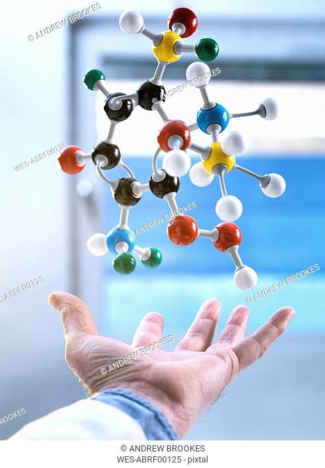 Hand and a floating molecular model, gravity