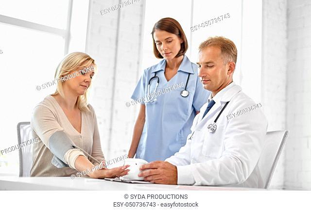 doctor measuring patient woman's blood pressure