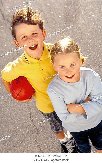 portrait, full-figure, blond girl with short plaits wearing grey sweater and freckeled boy with yellow t-shirt in the age of 5-6 years in the street with an...