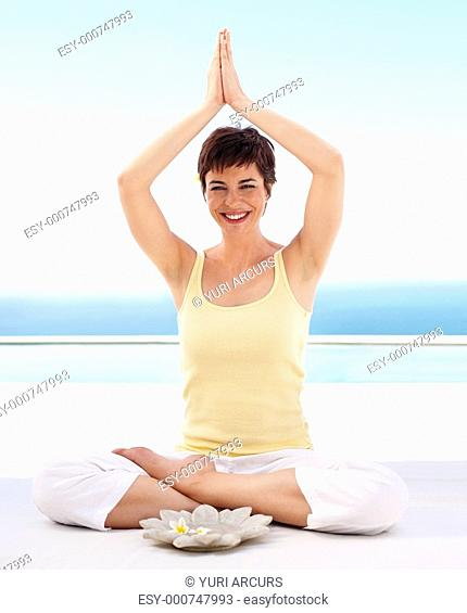 Young woman practicing yoga with hands raised in the air