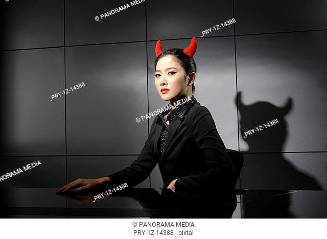 Young woman with red horns