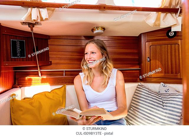 Young woman sitting in sailboat cabin with book