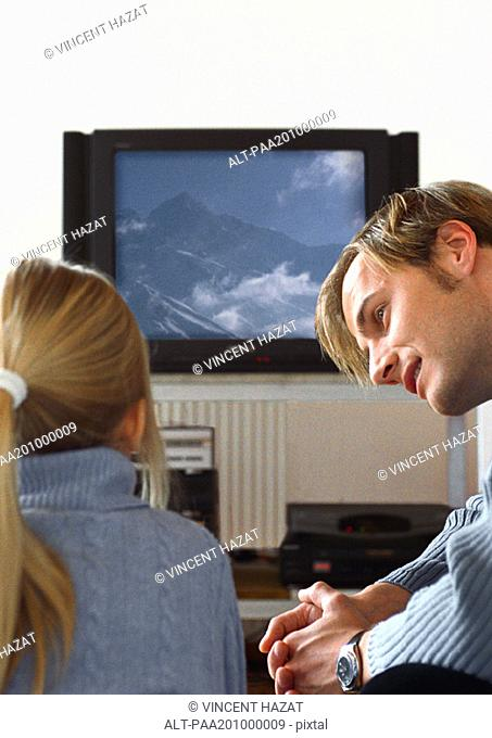 Father looking at daughter watching TV