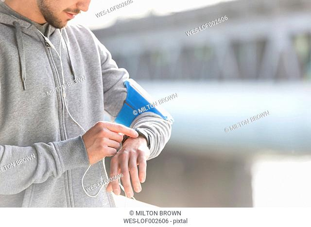 Young athletic man checking his watch