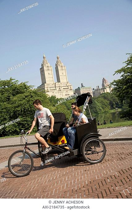 USA, New York State, Tourists in Pedicab overlooking water in Central Park; New York City