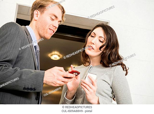 Office colleagues using cell phone by elevator