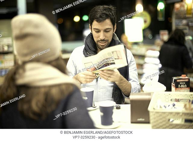 man looking at newspapers in hands, in coffee shop, couple, in Munich, Germany