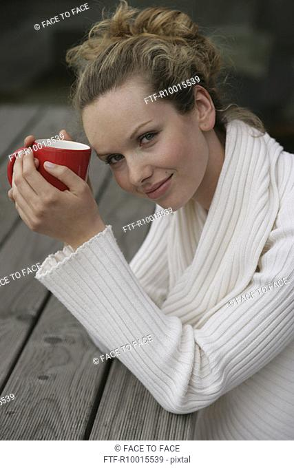 A blonde woman holding a red mug smiles at the camera