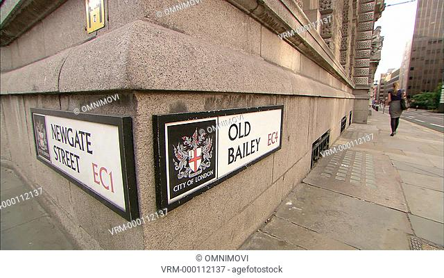 Old Bailey and Newgate Street signs on side of walls with woman walking along street and black taxis