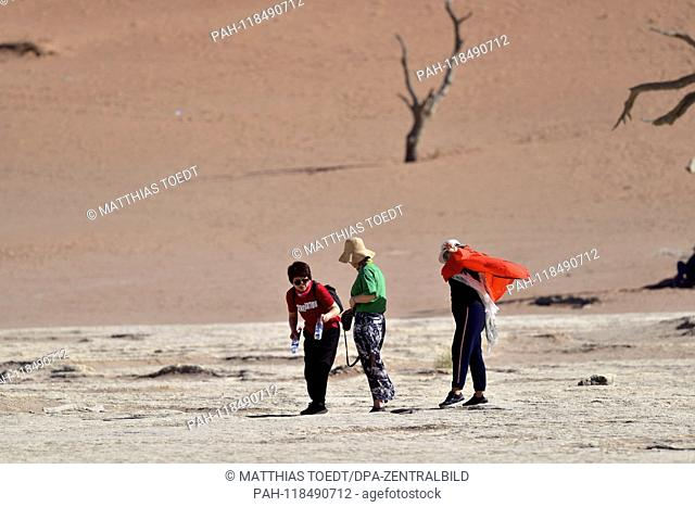 Asian tourists take a walk in Dead Vlei, taken on 01.03.2019. The Dead Vlei is a dry, surrounded by tall dune clay pan with numerous dead acacia trees in the...
