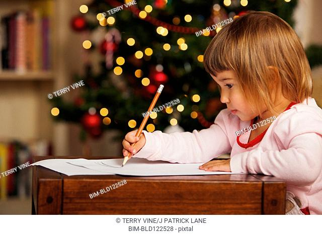 Mixed race girl writing letter to Santa Claus