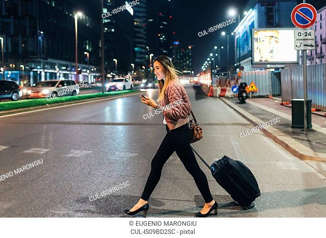Woman walking outdoors at night, pulling wheeled suitcase, holding smartphone