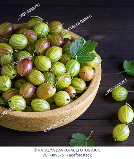 round wooden bowl with green gooseberries, brown table, top view