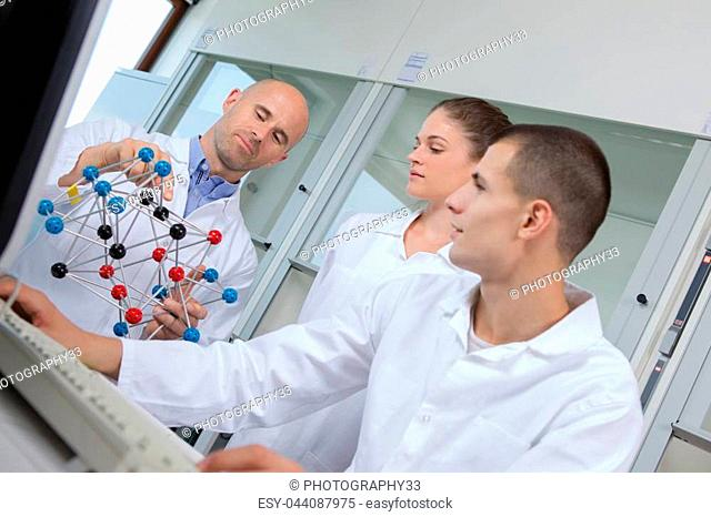 students with teacher holding molecular model