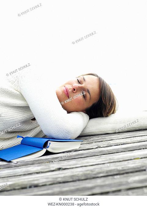 Germany, Munich, Mature woman relaxing on jetty near lake besides book