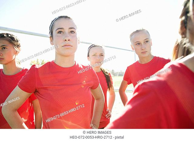 Soccer girls looking serious on sidelines