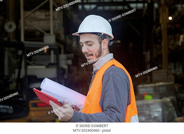 Young male engineer holding blueprint and using digital tablet at construction site, Freiburg Im Breisgau, Baden-Württemberg, Germany