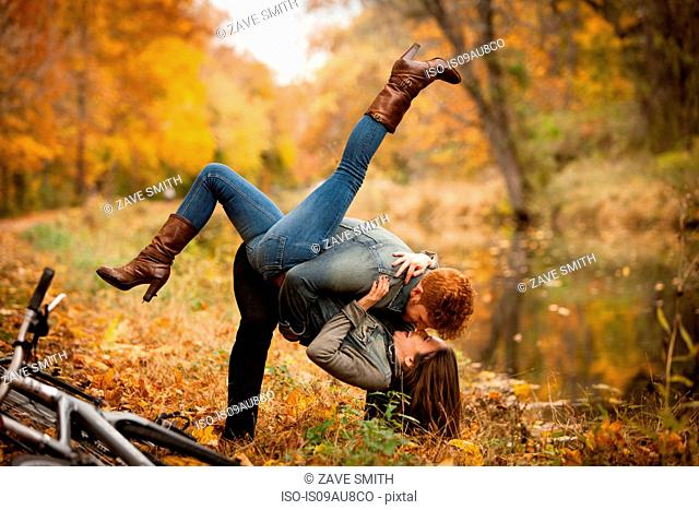 Romantic young couple fooling around on riverside in autumn