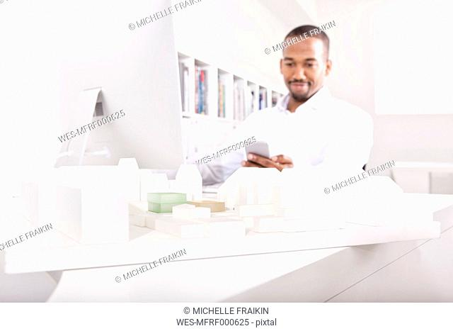 Architectural model on a desk at office with man looking at his smartphone in the background