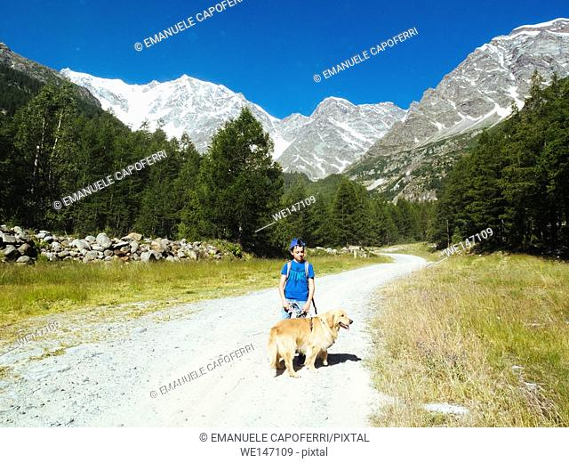 Boy and his dog in the mountains during a hike in the Mount Rose Valley, Macugnaga, Piedmont, Italy