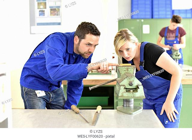 Instructor with trainee at workbench