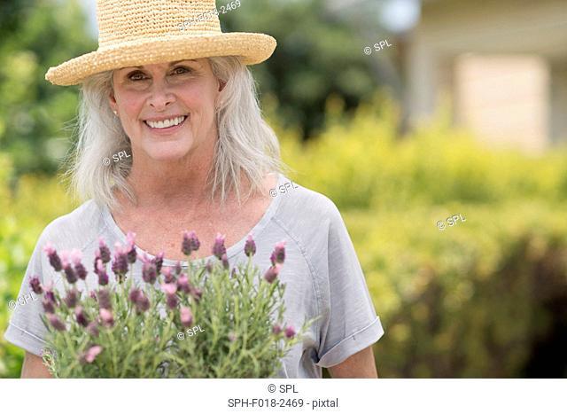 Senior woman holding pot plant