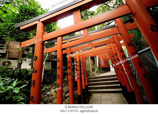 JAPAN, TOKYO, 11.07.2008, Access path by vermilion wooden torii. Gojo Tenjin Shinto Shrine, dedicated to the gods of medicine and learning